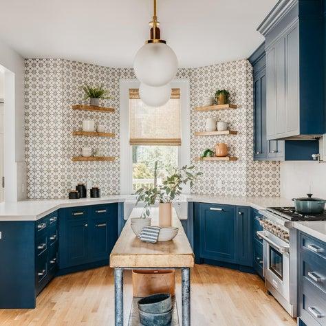 Blue and white kitchen with blue cabinets, patterned concrete tile backsplash.