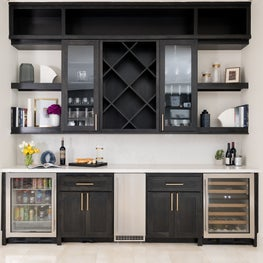 Dry bar area with ample storage, a mini fridge, plenty of counter space, and black stained cabinets