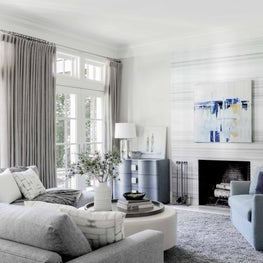 Modern family room with fireplace, abstract art, neutrals and pops of blue