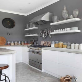 Open plan white kitchen in a converted stable featuring concrete top and floor
