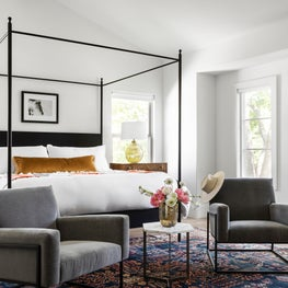 Eclectic master bedroom with a metal canopy bed and gray velvet club chairs