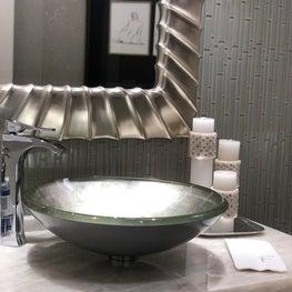 Powder room, vessel sink, metallic finish mirror, wall treatment, stone counter