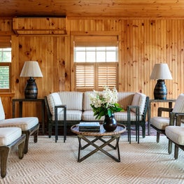 Rustic wood paneled walls in this neutral family room with mid century furnishings.
