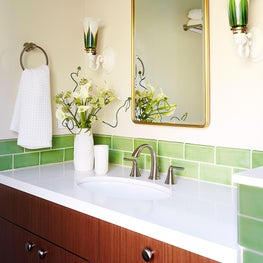 Master bathroom with green subway tile and vintage sconce lighting