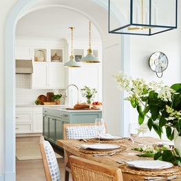 Blue and white dining room and kitchen with hanging lanterns and pendants