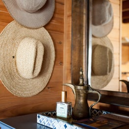 Detail of bedroom dresser with brass mirror and summer hats.