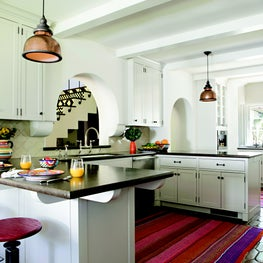 White kitchen with terra cotta tile floors and painted ceiling beams