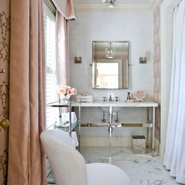 At Home toiletry area with marble floors, pink drapes