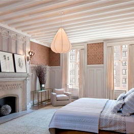 Master bedroom with pink fabric walls, paneling, ornate fireplace