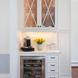 White inset bar in kitchen with lighted glass cabinet