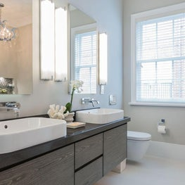 Contemporary bathroom with wall-mounted double vanity, faucets, and toilet