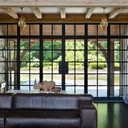Addition to Tudor House, Family Room with exposed rustic beams and steel windows