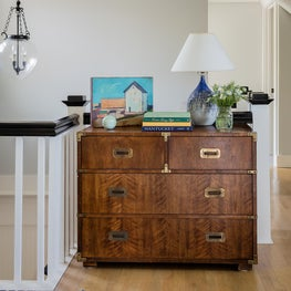 A Vintage campaign chest prominently positioned in a stair hall landing