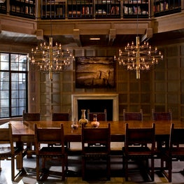 Grand double-height dining room with book-lined balcony