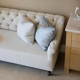 Neutral tufted sofa with marble top chest of drawers