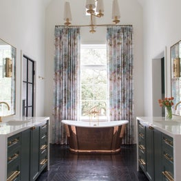 Soft, green watercolor fabric accentuates and softens an English copper tub.