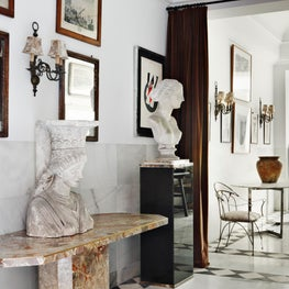 Foyer with marble tiles, eclectic art collection