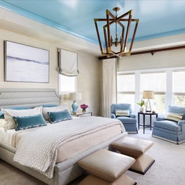 Elegant bedroom with painted blue ceiling, eclectic furniture, and blue accents
