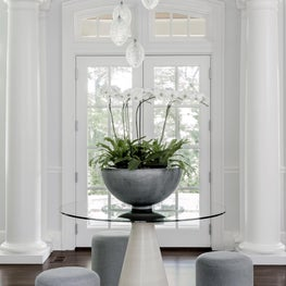 Spacious foyer with glass topped table, stools and glass pendants