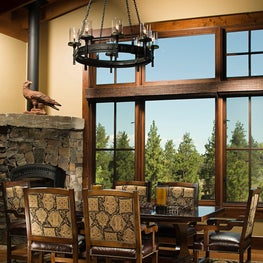 Mountain house dining area with stone fireplace, wagon wheel chandelier