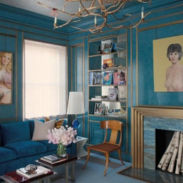 Peacock blue library with brass trim to highlight paintings by John Currin, illuminated by an organic chandelier by Claude Lalanne
