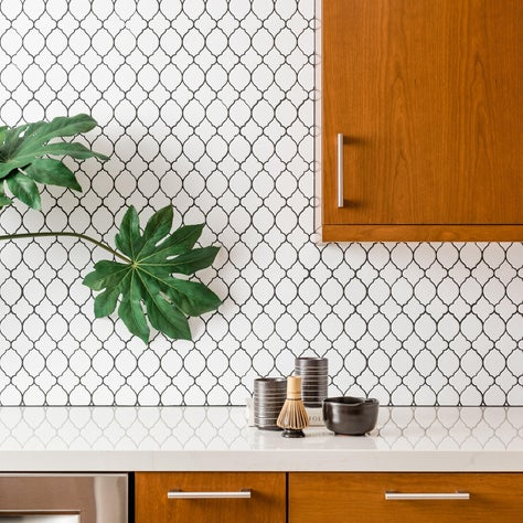 White patterned tile backsplash with light wooden cabinet accents