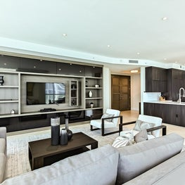 Contemporary great room with lighted custom builtins and neutral furniture.