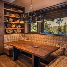 Dining nook with raw edge wood table and basketry decor