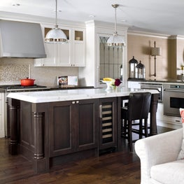 Traditional white kitchen with a walnut island and a mirrored fridge panel door.