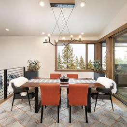 Dining room table, dining chairs, sheepskin throws, metal stair railing, large rug and linear chandelier