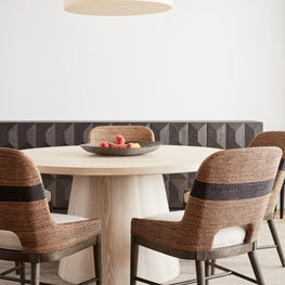 Pebble Beach seating. Neutral chair, wood sideboard, black lamp, and photography.