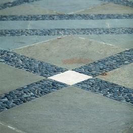 Pebble banding accents thr geometric bluestone paving pattern.