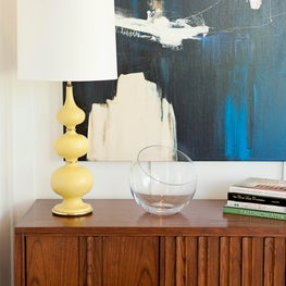 Mid-Century inspired console with vintage lamps and abstract art.
