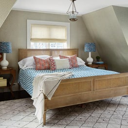 Asbury Master Bedroom with Moroccan Rug, Cane Bed, Eaves and Wallpaper