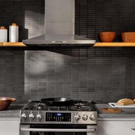 Kitchen with open shelving, black stone backsplash