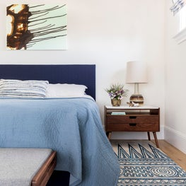 Vintage mid-century modern brass planters reminiscent of seashells accent the master bedroom in this seaside home. An abstract painting by Ruben Vincent defines the space above the bed.