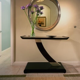 Oval mirror and unique table greet you in the entryway.