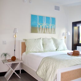 bedroom/white cane bed/green and blue bedding/gold and white lighting fixtures