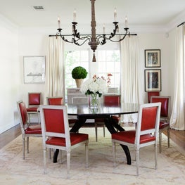 Traditional dining room with modern round table and antique red leather chairs