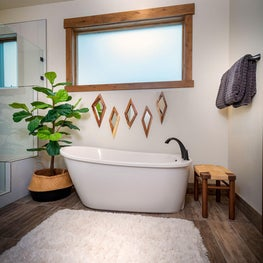 Freestanding white tub with wood mirror art above, wood stool, fluffy white rug, hardwood floor and trim