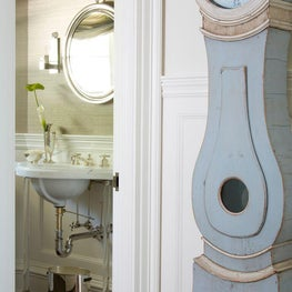 A Gustavian clock sits outside the powder room.
