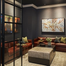 Media Room draped in rich wallcovering, navy lacquered ceilings and cognac leather seating.