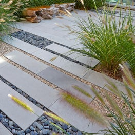 The front entrance layered with pavers, gravel bands, and Pennisetum grasses.