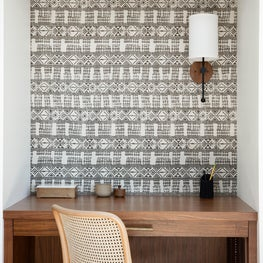 Built-in home office with black and white ethnic wallpaper and white cabinets