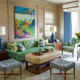 Bright living room with wooden walls and eclectic teal seating