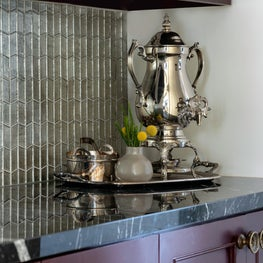 Silver serving tray in a glamorous Houston kitchen with black countertops