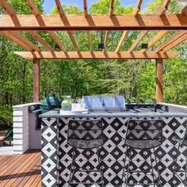 Hamptons outdoor kitchen with graphic cement tiles and cedar pergola