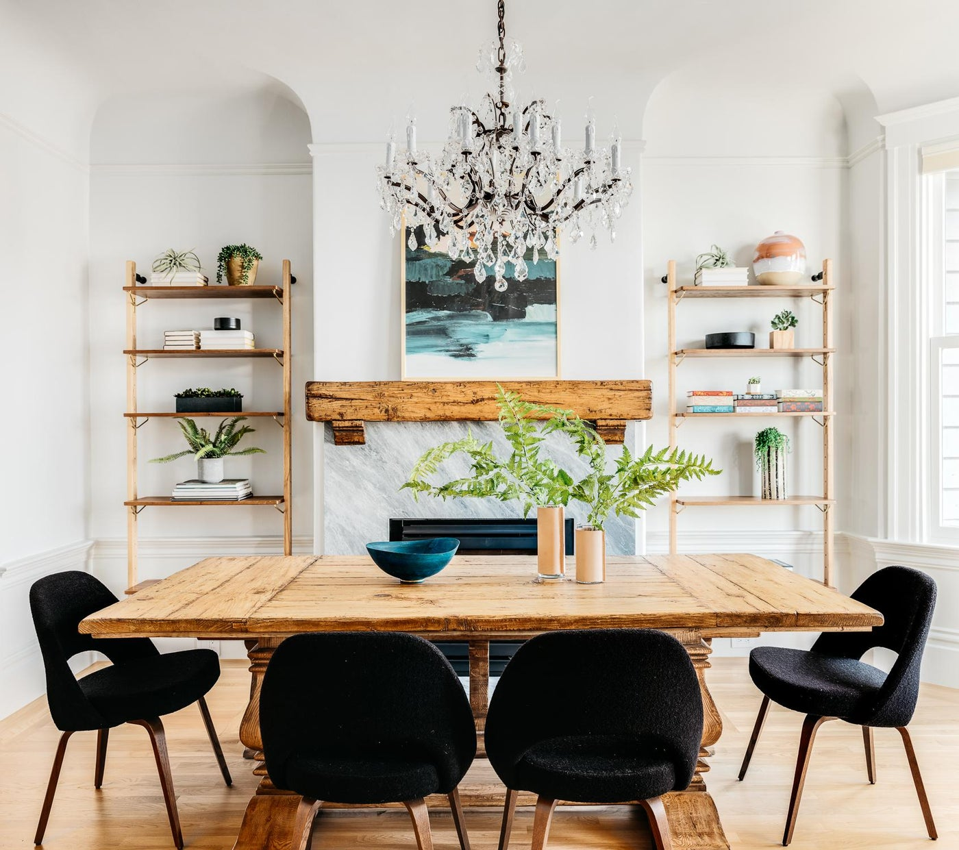 Rustic eclectic dining room with mid-century chairs and crystal chandelier.