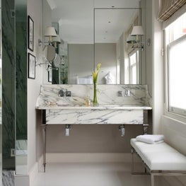 Chic townhouse bathroom with marble washstand and Ralph Lauren fabric