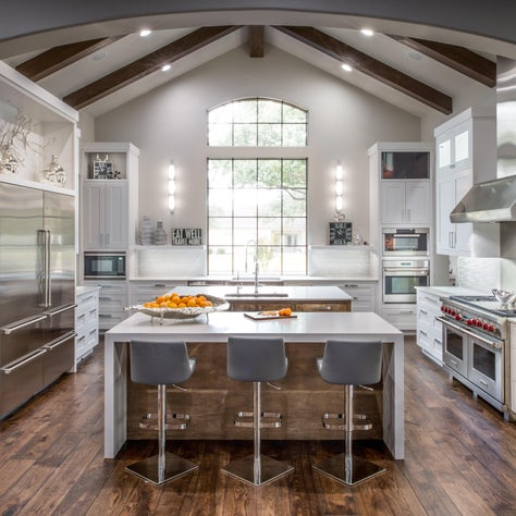 Fresh current white kitchen with open ceiling beams and double islands